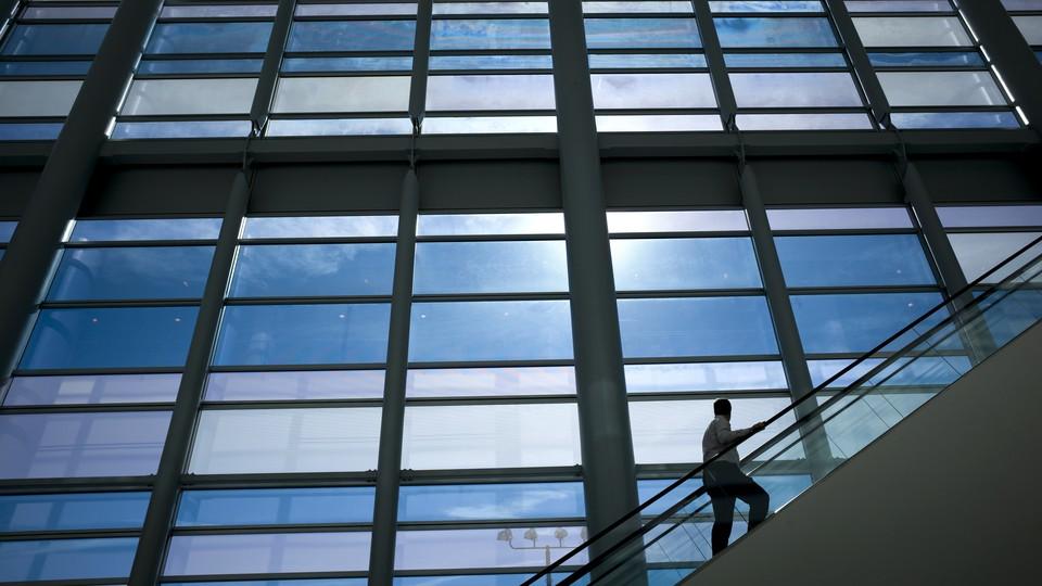 A man on an escalator looks at an enormous set of windows.
