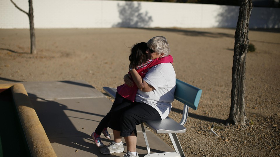 A young child hugs an older person sitting on a park bench.