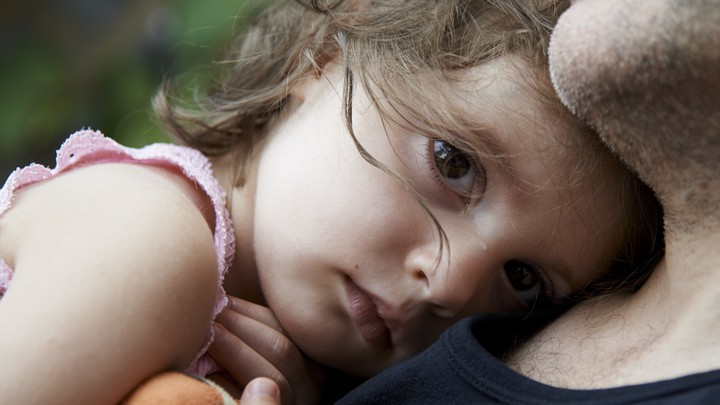 A tear streaks across sad child's nose as she rests her head on a man's chest.