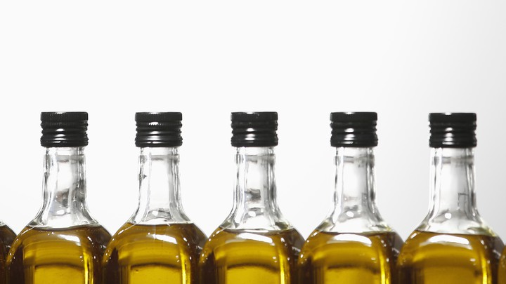 A close-up of bottles of olive oil against a white background