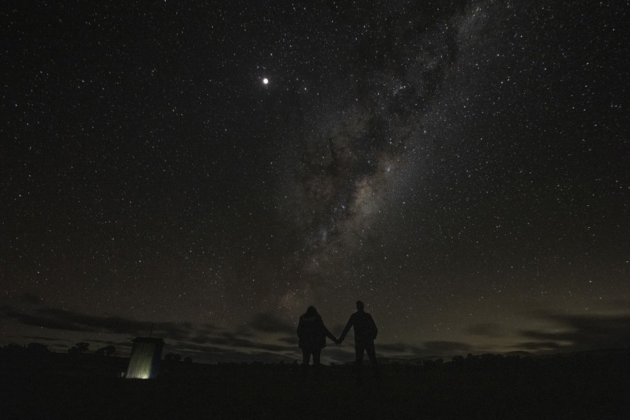 A couple stands outside beneath the Milky Way.