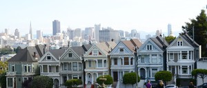 Victorian homes on a grassy hill with the San Francisco skyline in the background