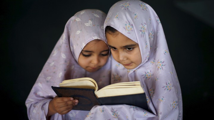 Two young girls reading the Quran