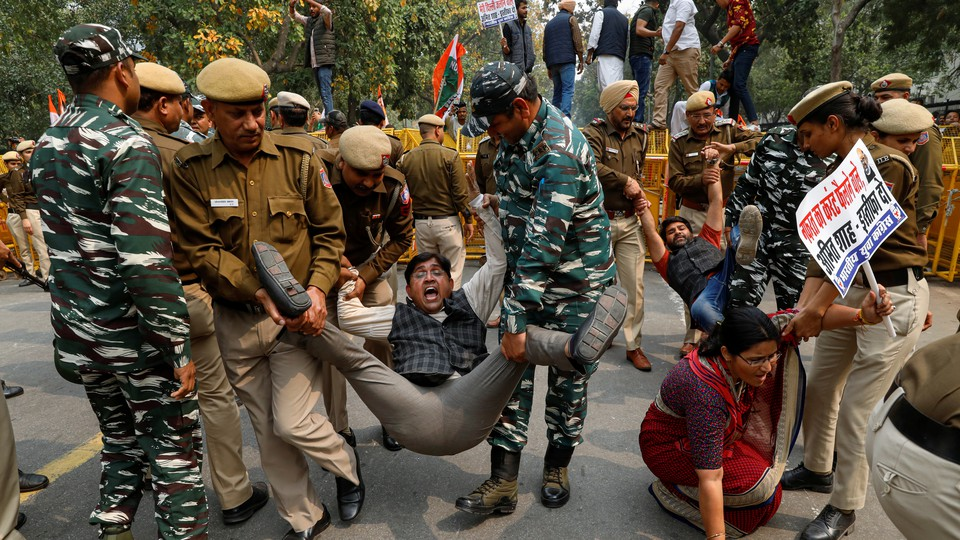Police detain activists during a protest in Delhi.