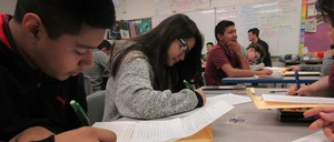 8th graders at Emiliano Zapata Academy pen down letters to kids at Amundsen High School.