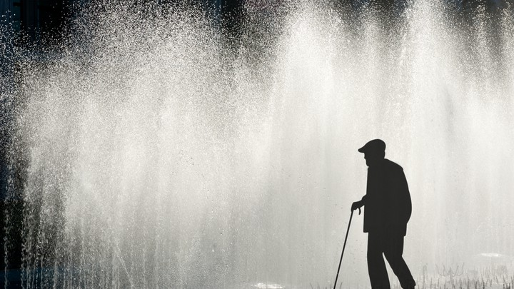 A man with a cane is silhouetted against water spraying from fountains.