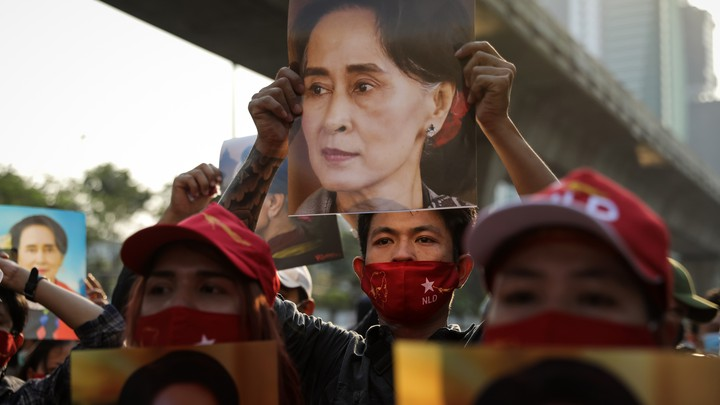 Protesters hold up an image of Aung San Suu Kyi out the Myanmar embassy in Bangkok.