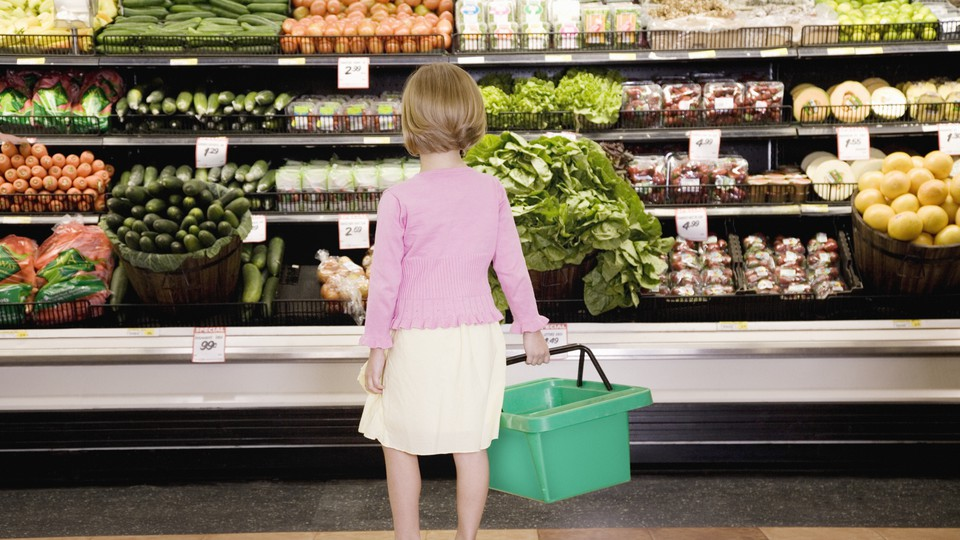 A young girl looks at the produce aisle in a grocery store.