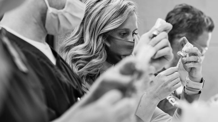 healthcare workers prepare doses of a COVID-19 vaccine