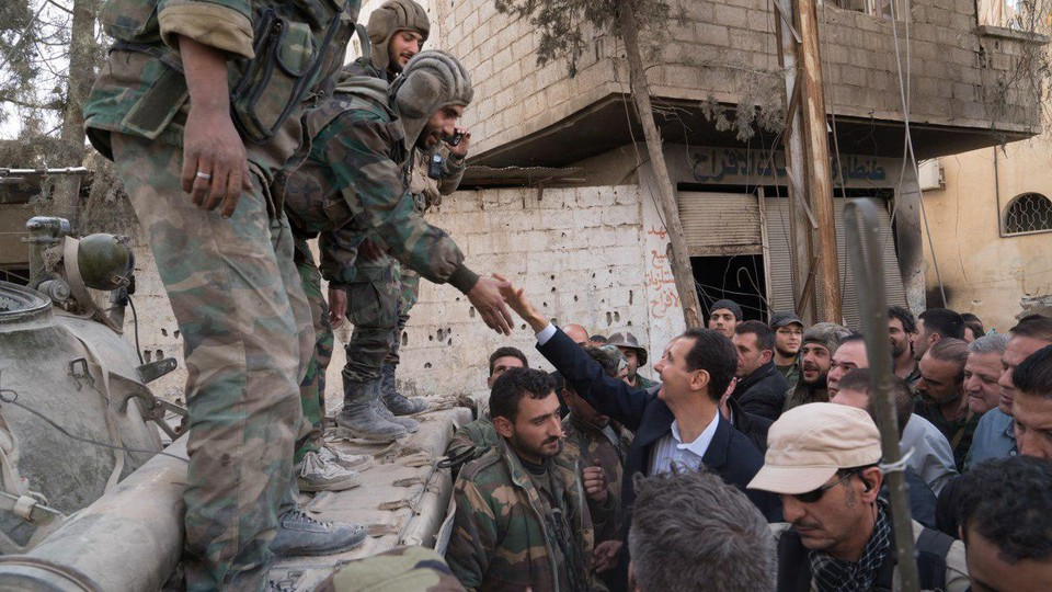 A soldier reaching down to shake President Assad's hand