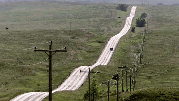 A road surrounded by green hills on the Pine Ridge Indian Reservation, in South Dakota