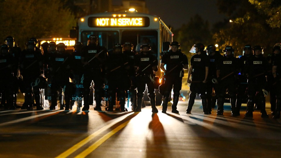 Riot police gather near protesters after a midnight curfew, as demonstrators gather by the police station to protest the police shooting of Keith Scott in Charlotte, North Carolina, U.S., September 24, 2016.