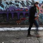 A man walks by a mural in Long Island City, Queens.