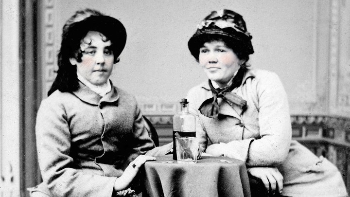A black-and-white photo of two 19th-century women sitting at a table with a bottle of whiskey and a cigar