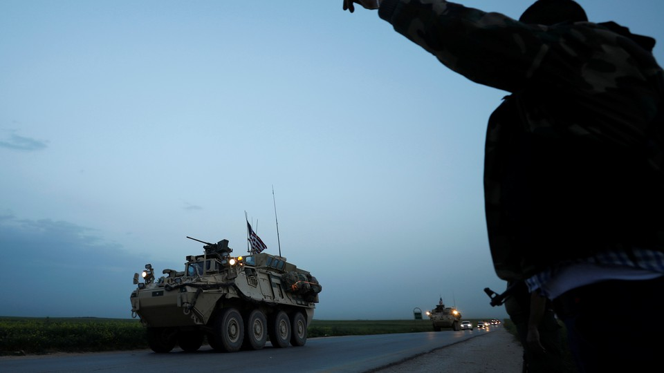 A Kurdish fighter from the People's Protection Units (YPG) gestures at a convoy of U.S military vehicles driving in the town of Darbasiya next to the Turkish border, Syria, on April 28, 2017.