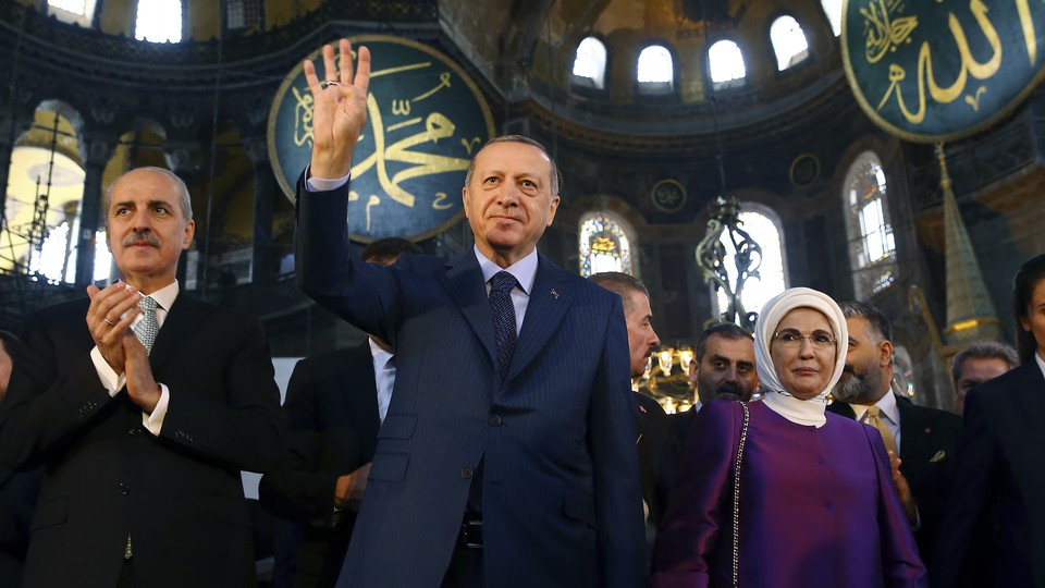 Erdoğan, center, accompanied by his wife, Emine, right, waves to supporters as he walks in the Byzantine-era Hagia Sophia, an UNESCO World Heritage site and one of Istanbul's main tourist attractions, in the historic Sultanahmet district of Istanbul. The sixth-century building is now at the center of a heated debate between conservative groups who want it to be reconverted into a mosque and those who believe the World Heritage site should remain a museum.