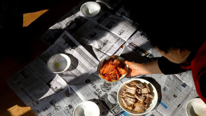 Woman placing bowel of kimchi on newspapers on the floor