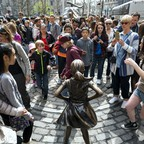 A crowd gathers to take pictures of the Fearless Girl statue across from Charging Bull in Manhattan's Financial District