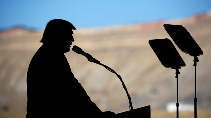 Donald Trump stands silhouetted against mountains in the background.