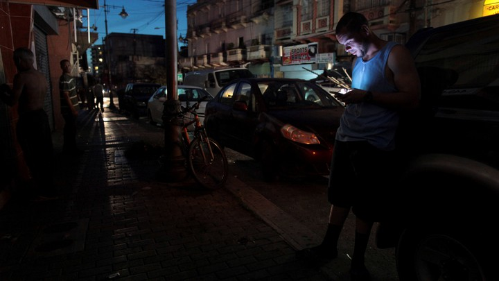 A man uses his phone during a blackout in San Juan, Puerto Rico.