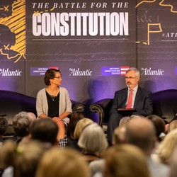 "Four people sit on a stage in front of a sign that reads ""The Battle for the Constitution"""