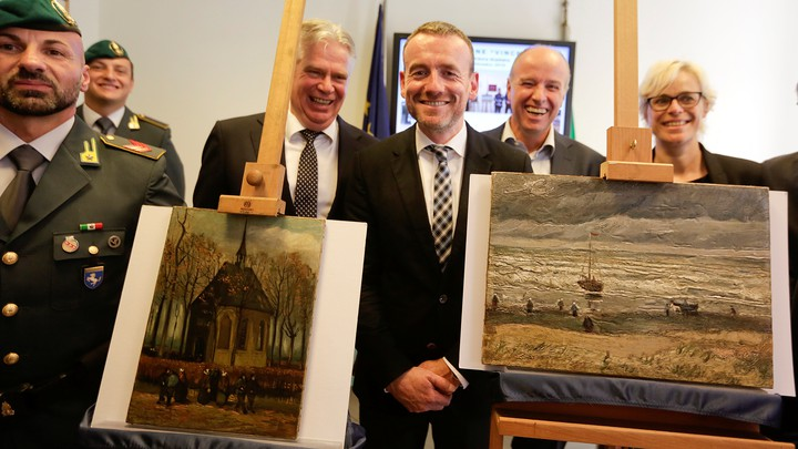 Axel Ruger, the director of the Van Gogh Museum in Amsterdam, poses between the two recovered paintings in Naples, Italy.