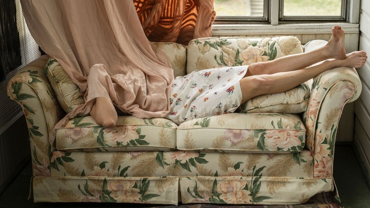 A woman lying on her couch, hiding her head