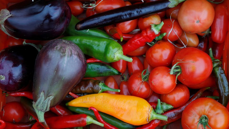 A basket of vegetables, including tomatoes, peppers, and eggplants.