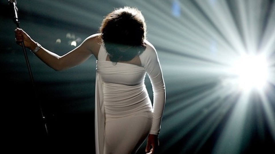 Whitney Houston in white, her head bowed, after a performance, on stage, with a spotlight at right