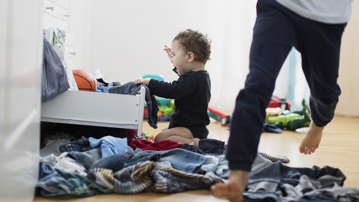 A child pulls clothes out of a drawer.