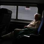 A photograph of a man sleeping on an Amtrak train near Birmingham, Alabama.