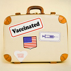 """A suitcase with stickers that say """"Vaccinated"""" and """"Covid Free"""" and with a sticker of a syringe and a U.S. flag"""