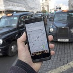 The Uber app is pictured in front of two London cabs.