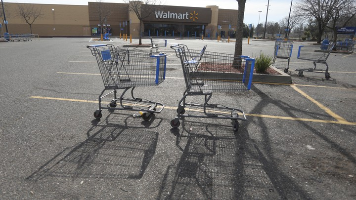 Shopping carts are shown in the parking lot of a Walmart store in California.