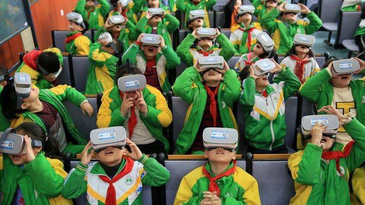 A group of kids in green and yellow school uniforms wearing VR headsets