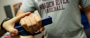 A teacher grabs a rubber training gun