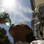 A girl drinks a bottle of water next to a fan spraying water mist on a hot summer day