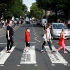 People cross in the crosswalk at Abbey Road.
