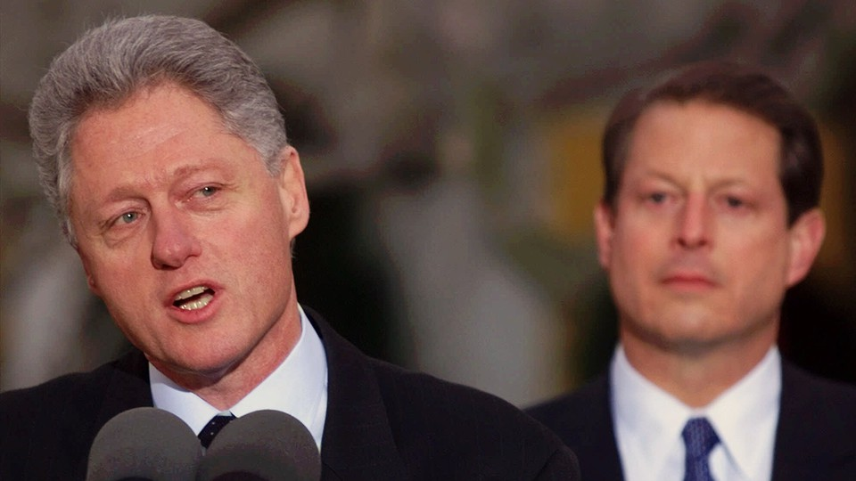 Bill Clinton speaking with Al Gore in the background