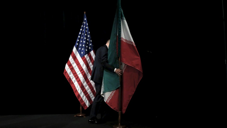 A staff member removes the Iranian flag from the stage next to the American flag.