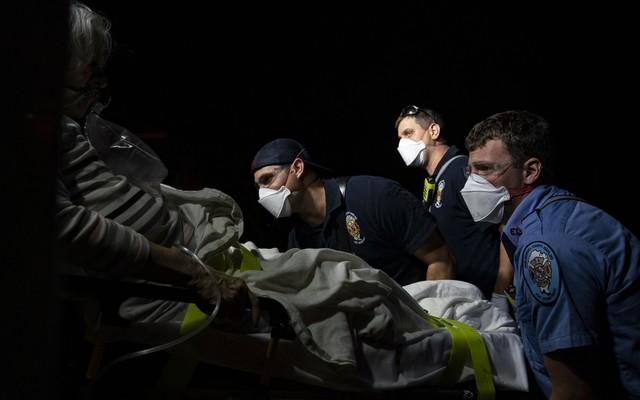 Paramedics prepare to transport a coronavirus patient to the hospital.
