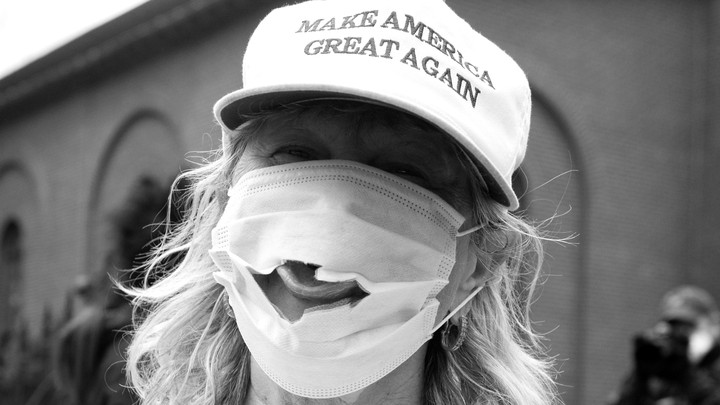 A woman wearing a Make America Great Again hat and a mask with a hole.