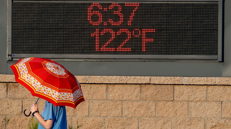 A person with an umbrella walking past an electronic sign showing the temperature to be 122 degrees Fahrenheit