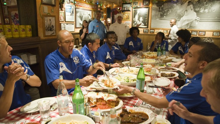 A soccer team eats a large spread at an Italian restaurant.