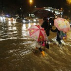 A woman and two children holding umbrellas cross a flooded street at night.