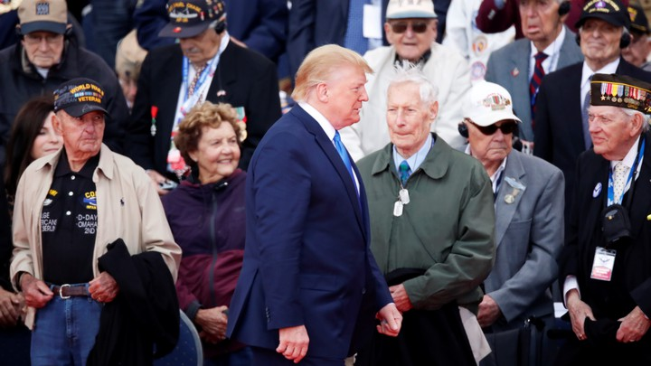 Donald Trump walks past World War II veterans at a D-Day ceremony in Normandy.