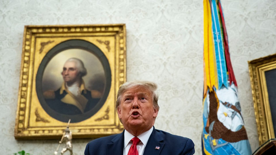 Trump sits in the Oval Office in front of a portrait of George Washington.