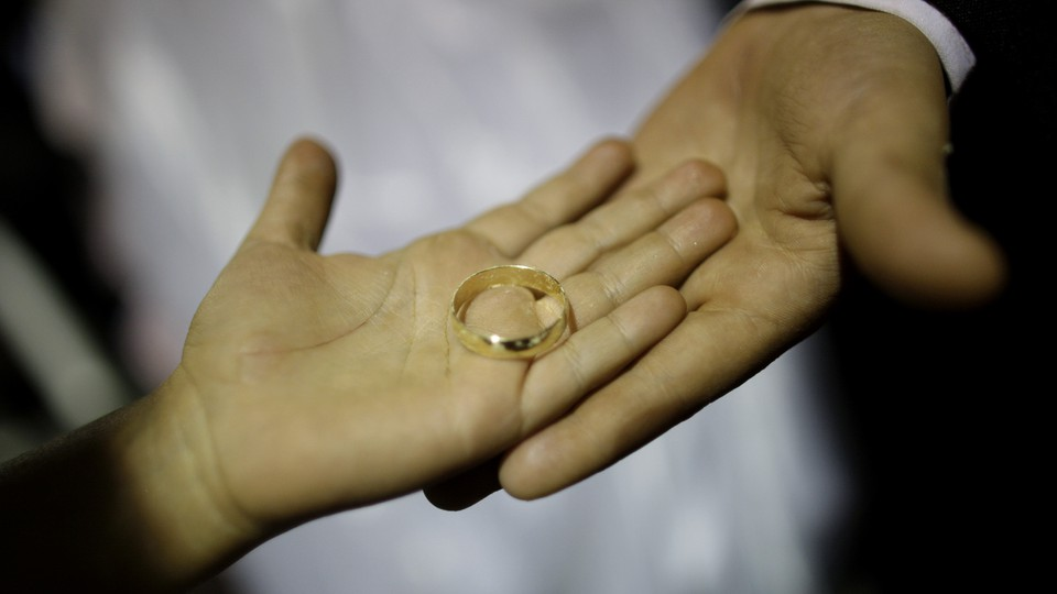 A small hand holding a gold wedding band rests on top of another person's larger hand.