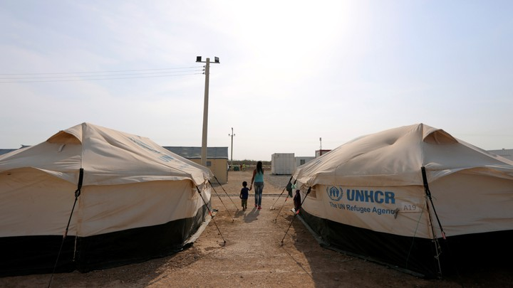 A woman walks hand in hand with her son in the middle of some tents in a camp run by the United Nations refugee agency (UNHCR) in Maicao, Colombia, on May 7, 2019.