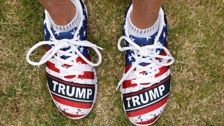 "A close-up of shoes monogrammed with ""Trump"" and an American flag"